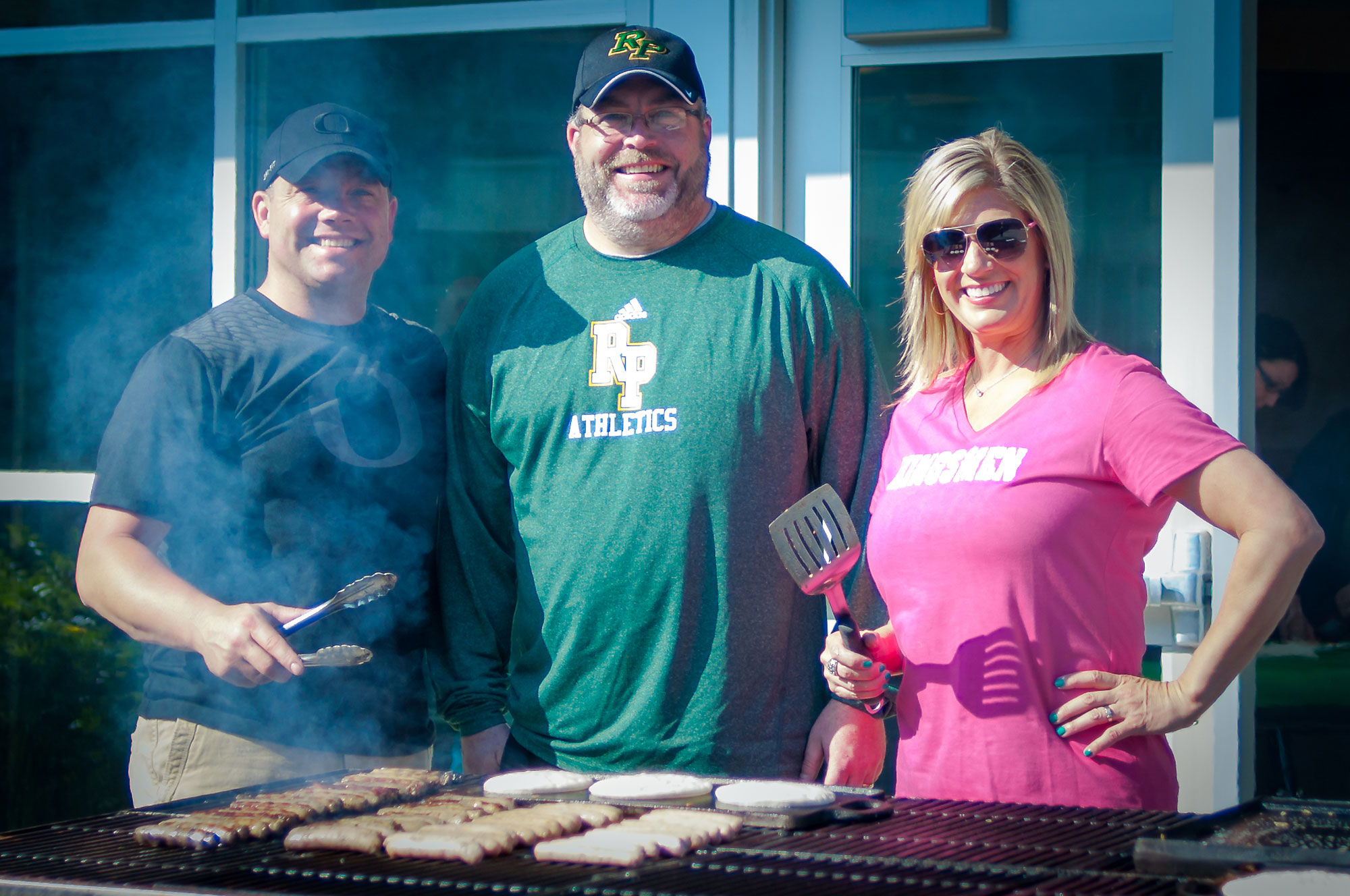 Gridiron members cooking pancakes and sausage on the BBQ grill.