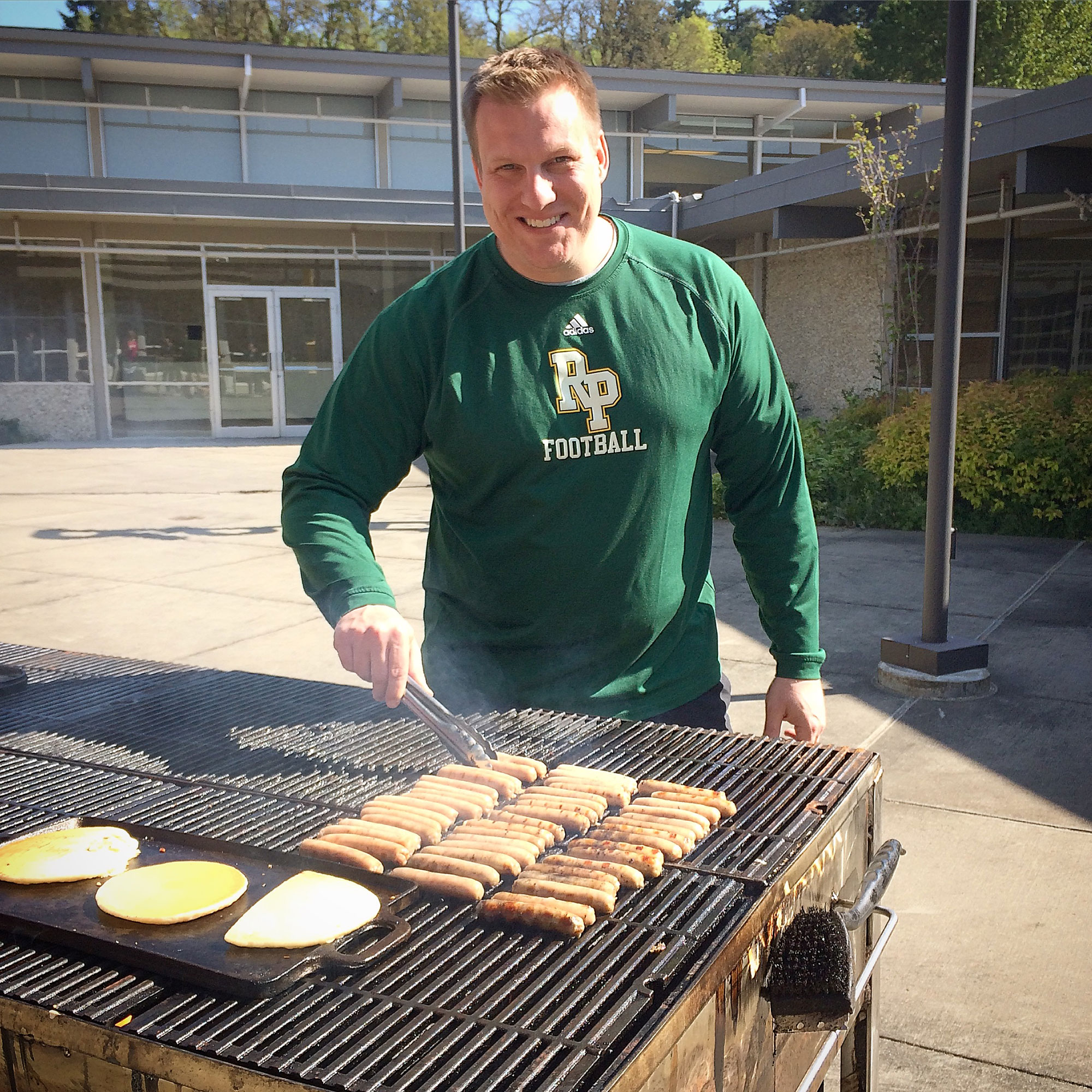 Coach Jacobs cooking sausages and pancakes on the BBQ grill.